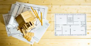 Building house. House construction. Many drawings for building, pencils and small wooden house on wooden background.