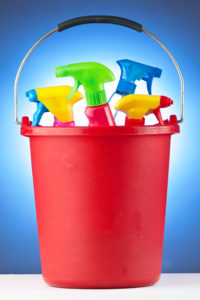 A red bucket filled with assorted cleaning supplies.
